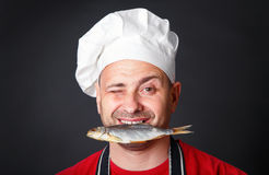 Funny cook in a hat with a dry fish in his teeth. Funny cook in a hat with a dry fish in his teeth in the studio on a black background Royalty Free Stock Image