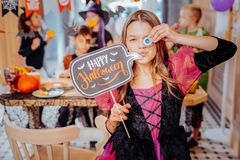 Funny cute schoolgirl holding funny cookies while attending Halloween party stock image