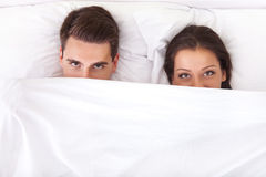 Funny couple in bed. Funny couple lying in bed with the sheet pulled up over their noses stock photo