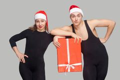 Funny couple in black dress and red christmas hat holding gift b. Ox together and looking at camera. Indoor studio shot, isolated on gray background royalty free stock photo
