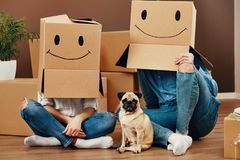 Funny Couple With Boxes On Heads. Funny Couple With Cardboard Boxes On Heads With Smiley Face Sitting On Floor With Dog In New Home. High Resolution royalty free stock photo