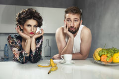 Funny couple after breakfast. Strange faces. Young men and beauty women in kitchen stock photography