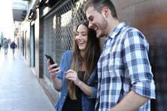 Funny couple checking smart phone content in the street stock photos
