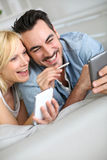 Funny couple comparing smartphones at home Stock Photo