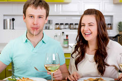 Funny couple eating macaroni at the kitchen with wine and salad Stock Photo