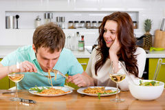 Funny couple eating spagetti at the kitchen with wine Stock Photo
