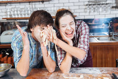 Funny couple with flour on faces having fun using dough. Funny young couple with flour on their faces having fun with dough on the kitchen stock photography