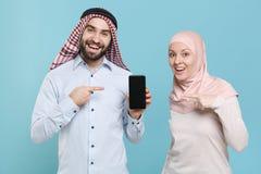Funny couple friends arabian muslim man wonam in keffiyeh kafiya ring igal agal hijab clothes isolated on blue