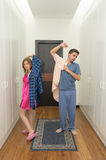 Funny couple getting dressed in pijamas Stock Images