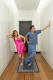 Funny couple getting dressed in pijamas Royalty Free Stock Photo