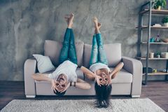 Funny couple with glasses gesturing is lying upside-down on the. Sofa at home. They are so cheerful, having fun together, go crazy, brother and sister stock image