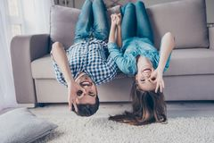 Funny couple with glasses gesturing is lying upside-down on the. Sofa at home. They are so cheerful, having fun together, go crazy, brother and sister stock images