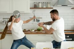 Funny couple having fun fighting with kitchen utensils cooking t. Funny couple pretending fight with utensils tools while cooking at home together, husband and royalty free stock images