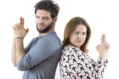 Funny Couple. Having tough expression, holding imaginary guns standing back to back stock image