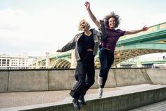 Funny couple junping near the Southwark bridge over River Thames, London. UK stock images