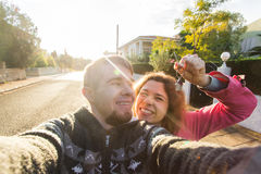 Funny couple With Keys Standing Outside New Home. Real estate, owner and people concept Royalty Free Stock Photos