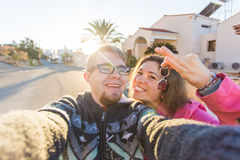 Funny couple With Keys Standing Outside New Home. Real estate, owner and people concept.  Stock Photography
