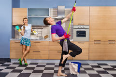 Funny couple on kitchen. Modern kitchen - women with sponge and smiling young men cleaning the floor at home and pretend to sing song with mop royalty free stock photo