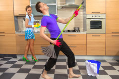 Funny couple on kitchen. Modern kitchen - women with sponge and smiling young men cleaning the floor at home and pretend to sing song with mop royalty free stock photos