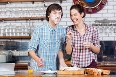 Funny couple kneading dough and having fun on kitchen Royalty Free Stock Images