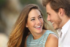 Funny couple laughing with a white perfect smile. And looking each other outdoors with unfocused background stock photos