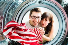 Funny couple loading clothes to washing machine Stock Photo