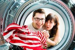 Funny couple loading clothes to washing machine Stock Photo