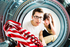 Funny couple loading clothes to washing machine Stock Image