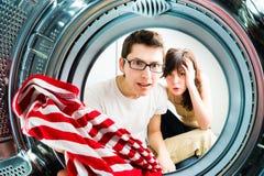 Funny couple loading clothes to washing machine Stock Image