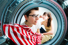 Funny couple loading clothes to washing machine Royalty Free Stock Photos