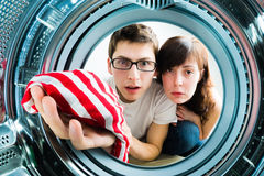 Funny couple loading clothes to washing machine Royalty Free Stock Photo