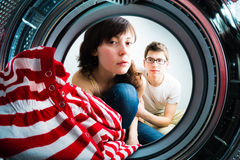Funny couple loading clothes to washing machine Royalty Free Stock Image