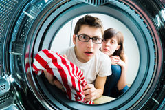 Funny couple loading clothes to washing machine Stock Images