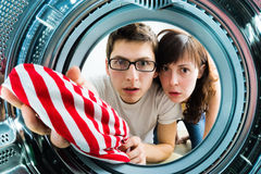 Funny couple loading clothes to washing machine Royalty Free Stock Photography