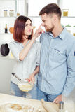 Funny Couple in love cooking dough and having fun with flour in  kitchen Stock Photos