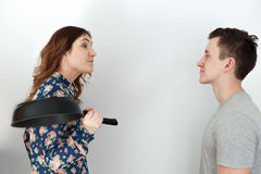 Funny couple, man against woman with a frying pan Royalty Free Stock Images