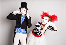 Funny couple of mimes talking by the phones. Concept of  April Fools Day. Funny couple of mimes talking by the phones. Concept of  April Fools Day Royalty Free Stock Photography