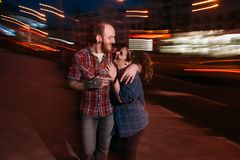 Funny couple in motion. Youth nightlife. Romantic date outdoors, blurred lights urban background. Happy laughing people, fun concept Stock Image