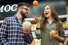 Funny couple playing with fruits Royalty Free Stock Image