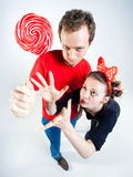 Funny couple playing with a lollipop in the studio Royalty Free Stock Photo
