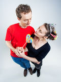 Funny couple playing with a lollipop in the studio Stock Image