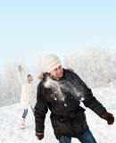 Funny couple playing snowballs Stock Photography