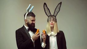 Funny couple rabbit eat carrot. Bunny ears concept with bunny couple. Heppy easter couple.