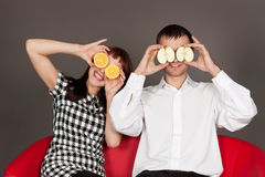 Funny couple shutting eyes with apple and orange Royalty Free Stock Photos