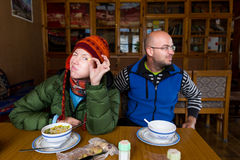 Funny couple sitting guesthouse dining room, eating noodles meal Stock Photography