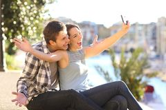 Funny couple taking selfies on vacation. Funny couple taking selfies with a smart phone outdoors on summer vacation Royalty Free Stock Image