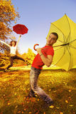 Funny couple with umbrellas. On autumn background royalty free stock images