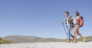 Funny couple walking with trekking poles Royalty Free Stock Photos