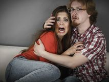 Funny couple watching horror movie Royalty Free Stock Photo