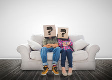 Funny couple wearing boxes with question mark on their head. On a couch royalty free stock photography